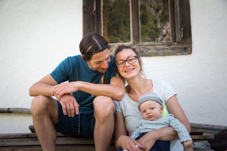 Claudia und Hubertus Lindner sitzen gemeinsam mit ihrem Sohn Darius vor einer Holzhütte in Gramais.