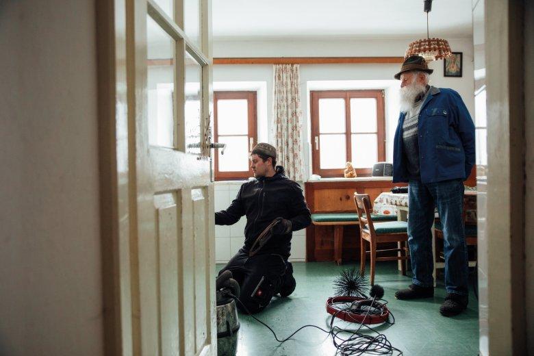 Kaminkehrer Simon Henökl überprüft die Heizung bei seinem Kunden Alfred Larcher.