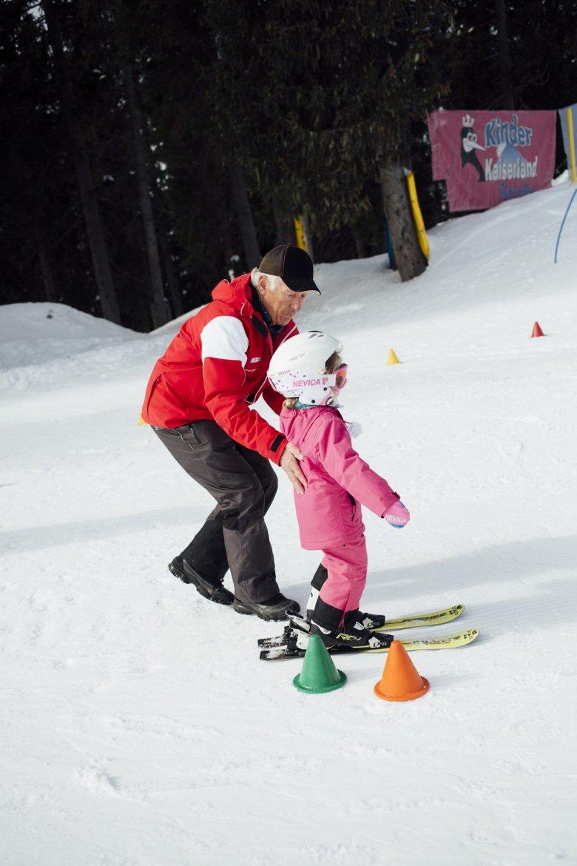 """Skischulleiter Told hilft einer kleinen Schülerin. Sie soll auf Skiern durch einen Parcours aus Hütchen manövrieren. """"Ein bisschen Rumrutschen, ein Gefühl für die Skier bekommen – mehr braucht es am Anfang nicht"""", sagt Told."""