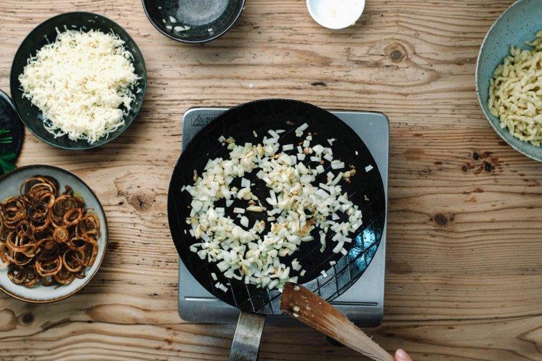Schritt 4: Zwiebel-Würfel in einer Pfanne mit Butter anrösten, die Spatzln in die Pfanne geben, Käse unterheben und schmelzen lassen.