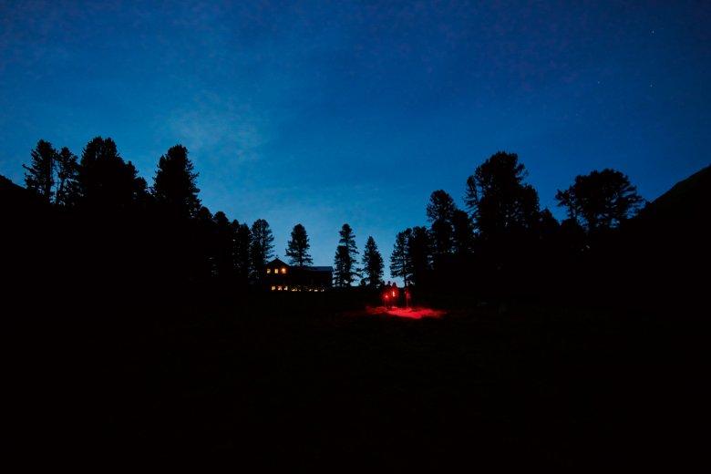 Nachtwanderer unterwegs mit Rotlicht-Taschenlampen in den Ötztaler Alpen.