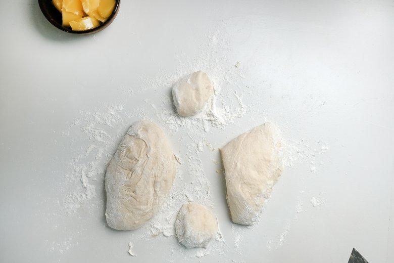 Den fertigen Teig mit viel Mehl auf eine Arbeitsfläche geben, durchkneten und handtellergroße Stücke schneiden.