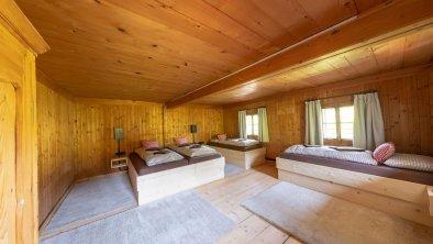 Schlafzimmer mit vier Betten und Fernseher - Gross