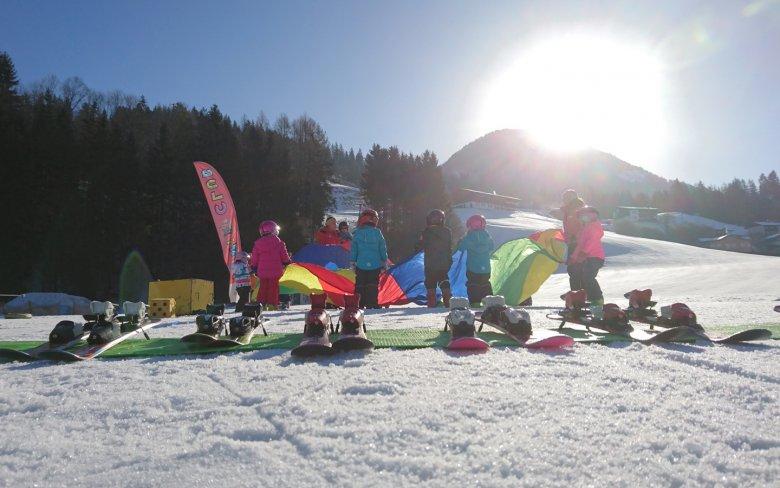 Mit lockeren Aufwärmübgungen werden die Kinder auf das Skifahren eingestimmt