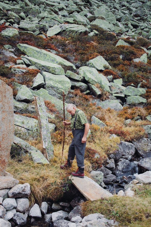 Erich Gatt vor dem Steinfeld unweit der Alm. Die grünliche Farbe stammt von Flechten, die über die Steine gewachsen sind.