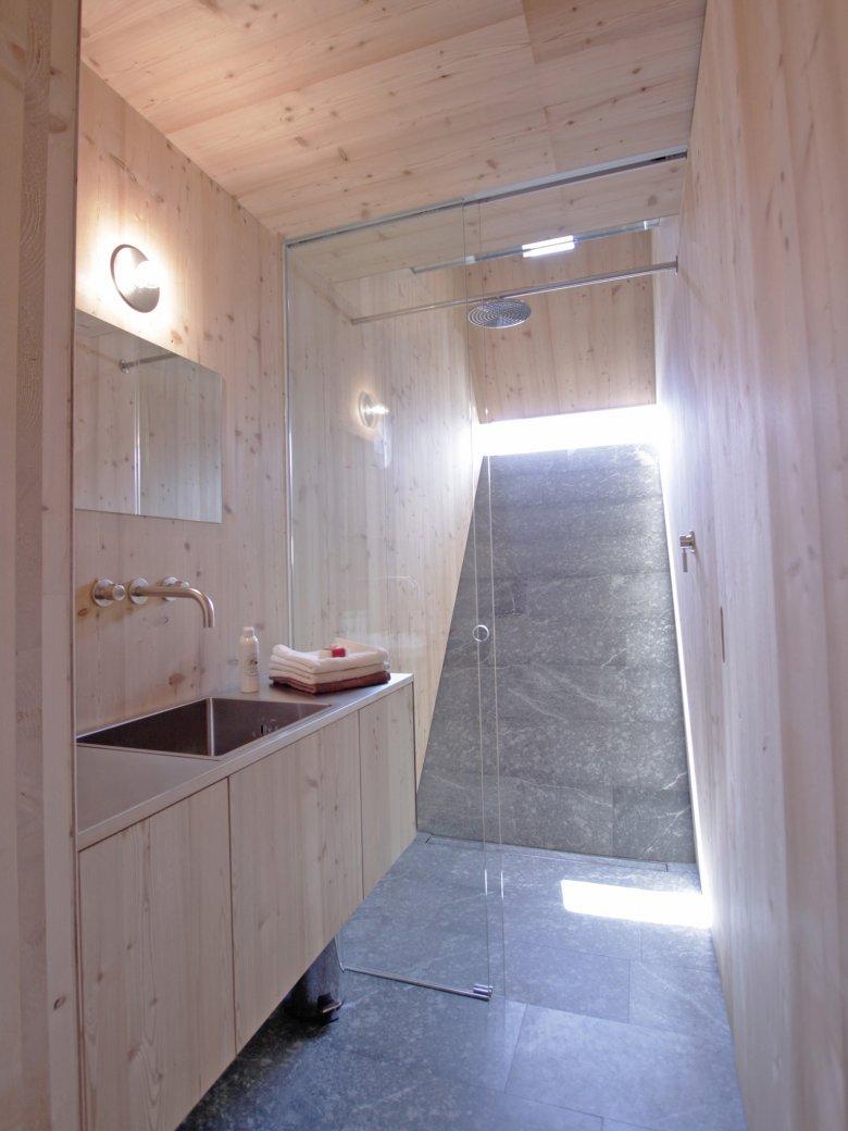 Ein reduziert-edles Badezimmer mit gläserner Dusche und kleinem Aussichtsschlitz ins Freie. Foto: Thomas Pitterl