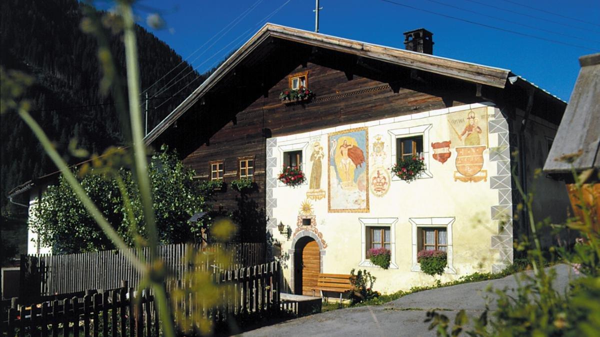 """Im Weiler Niederhof steht das """"Bürgerhaus Beim Tonesn"""", das eines der ältesten Häuser des ganzen Paznaun ist. Die Fassadenmalereien zeigen unter andere mehrere Heilige und stammen aus dem Jahr 1631., © Paznaun-Ischgl"""