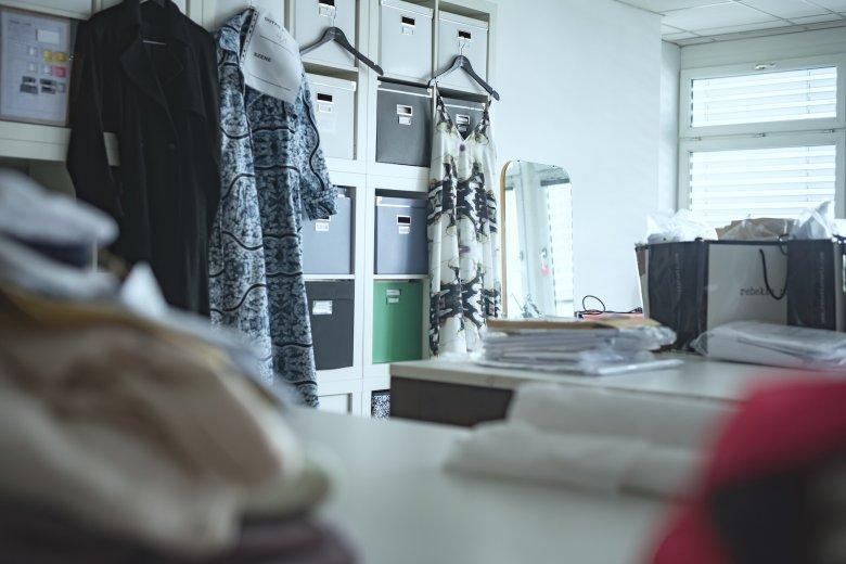 Im Atelier warten Mäntel und ein Kleid auf die weitere Verarbeitung.