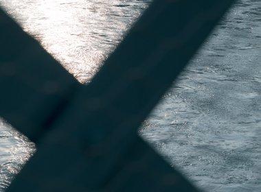Der Inn bei Innsbruck. Das Kreuz im Vordergrund stammt von einem Brückengeländer.