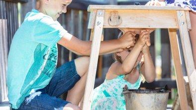 Kinder melken am Gummieuter