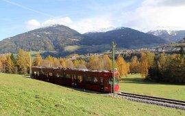 Idyllische Fahrt von Innsbruck nach Fulpmes im Stubaital: Hier tuckert die Straßenbahn über die Telfer Wiesen. Im Hintergrund sieht man den schneebedeckten Patscherkofel. (Foto: Haisjackl)