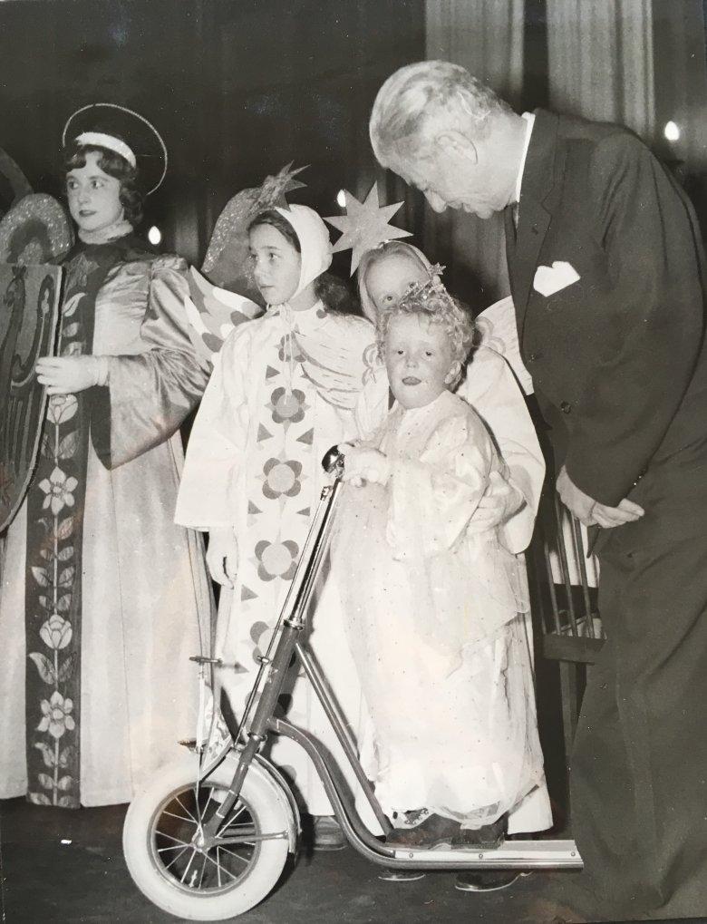 Ein sichtlich entzücktes Christkind beim Innsbrucker Christkindlempfang mit dem damaligen Landeshauptmann Hans Tschiggfrey, 1959: Der Roller war's. Bildquelle: Tiroler Landesarchiv