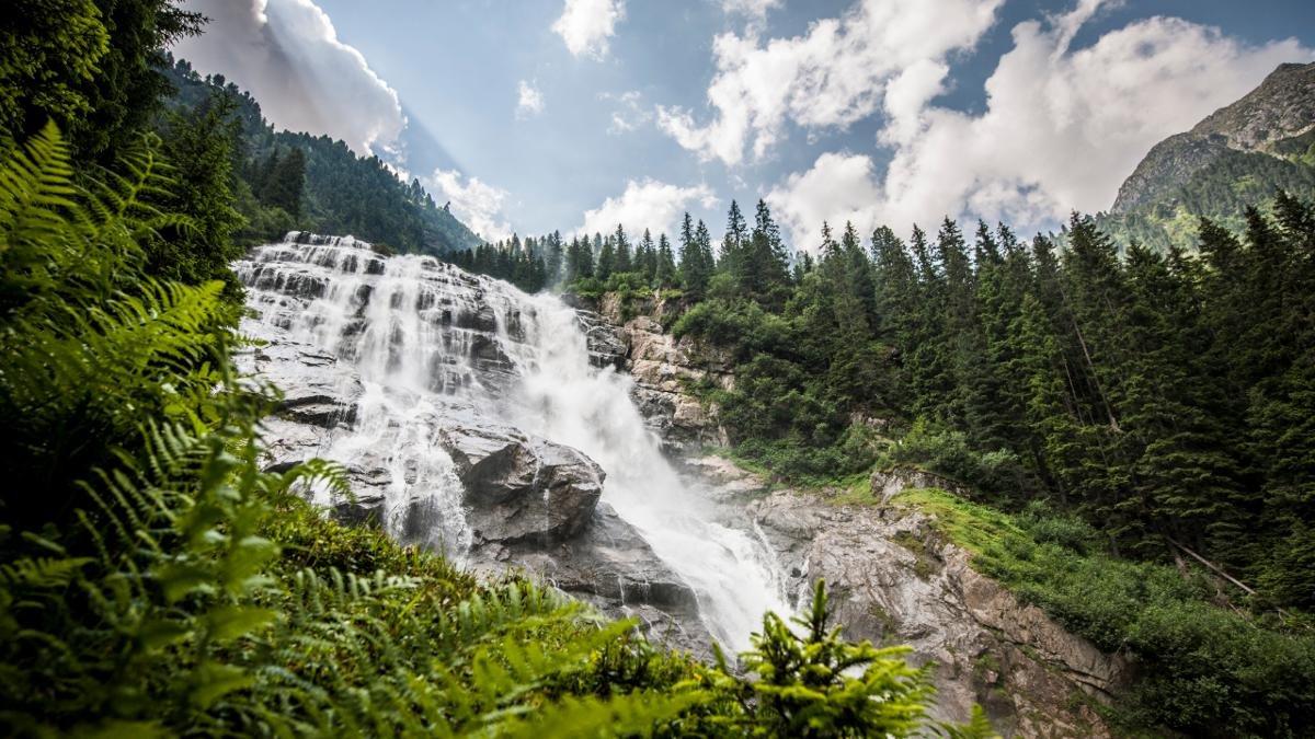 """Seine mächtige Breite von 85 Metern macht den Grawa-Wasserfall im hinteren Stubaital zum breitesten der gesamten Ostalpen. Über einen 180 Meter hohen Felsrücken ergießt sich hier der Sulzaubach. Das Naturschauspiel ist über den """"WildeWasserWeg"""" erreichbar., © TVB Stubai Tirol"""