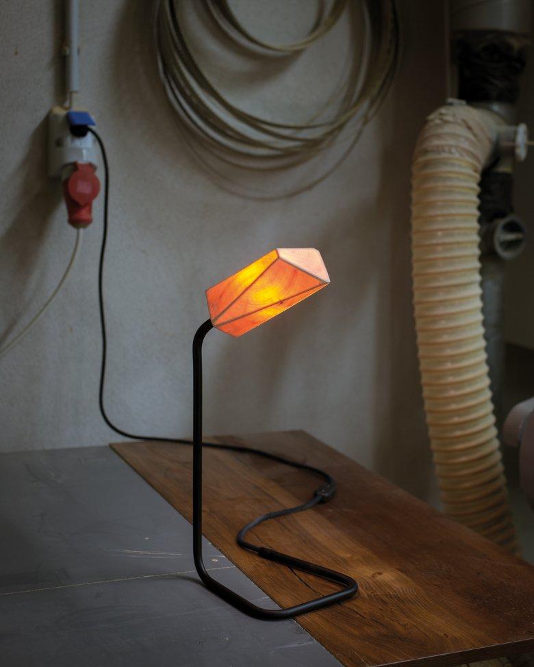 Das Licht dringt teilweise durch die Holzfasern. Von den Spektralfarben schafft es nur das orange und rote Licht auf die andere Seite.