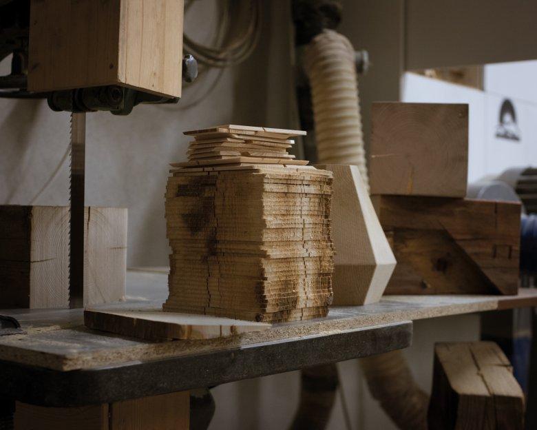 Die Hängeleuchte H2 besteht aus übereinandergeschichteten Altholzscheiben.