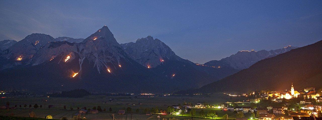 Im Talkessel von Ehrwald bietet sich ein freier Blick auf die vielen Sonnwendfeuer in der Tiroler Zugspitz Arena, © Albin Niederstrasser