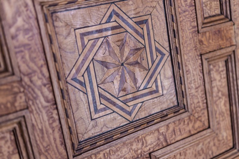 """Einlegearbeiten und Schnitzereien gibt es überall im Schloss. An der Decke im Königinzimmer arbeiteten """"sieben Tischlermeistern mit sieben Gesellen in sieben Jahren und sieben Monaten""""."""