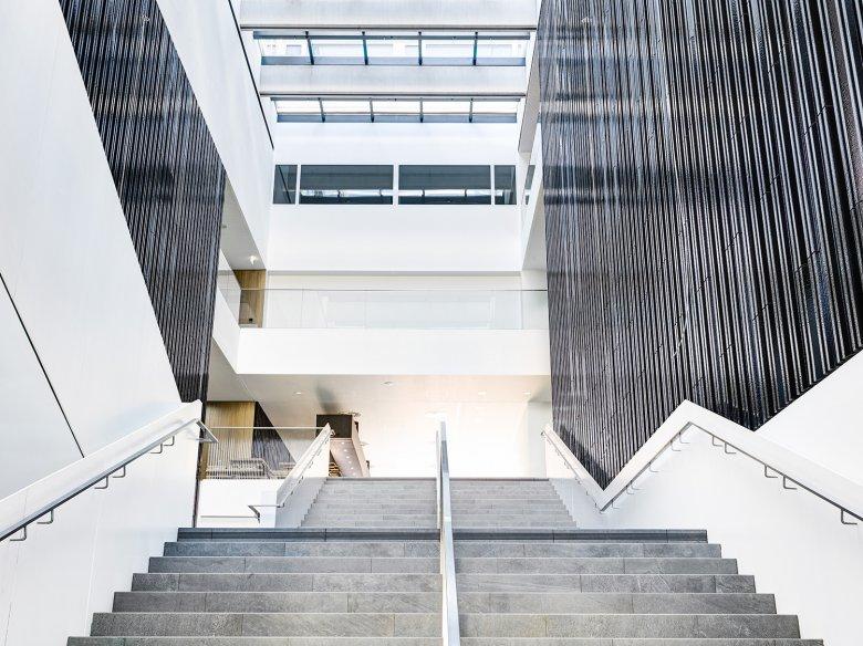 Panoramatreppe im Eingangsbereich. Im Inneren dominieren Glas, helle Materialien und natürliches Licht.
