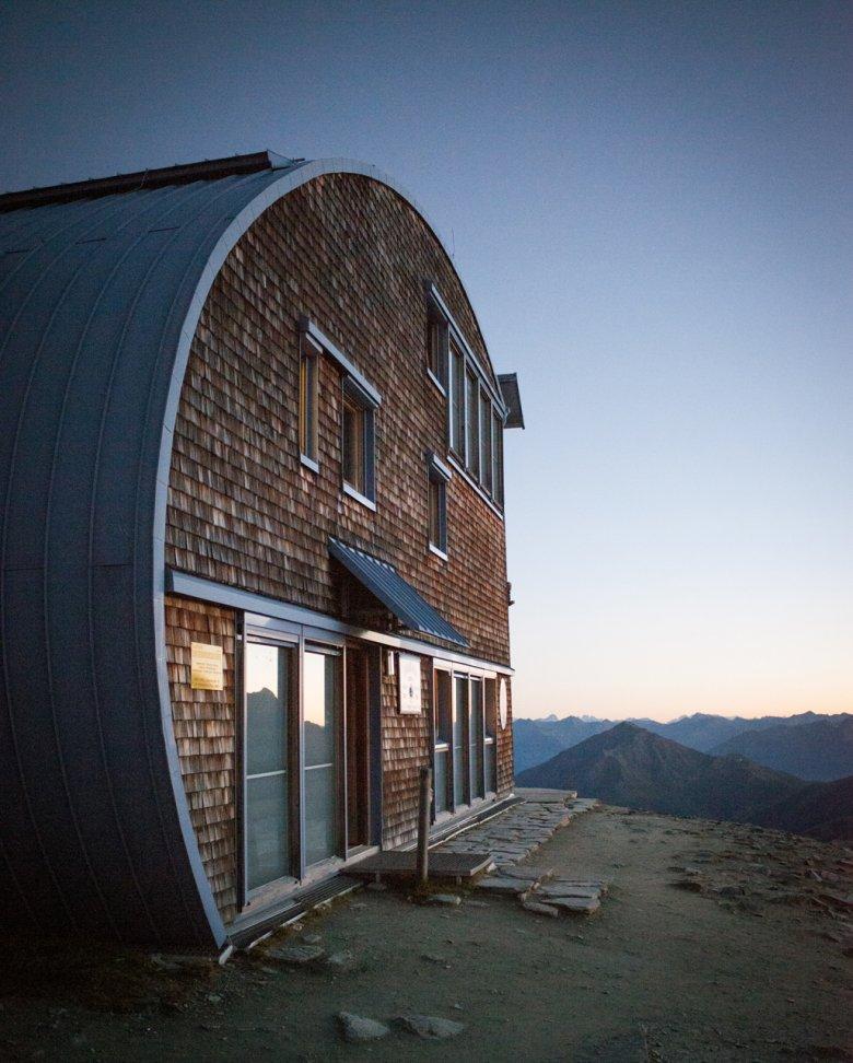 Ein angeschnittenes, auf der Seite liegendes Ei: Die markante Architektur vereint Hightech-Wetterschutz und sehr traditionelle Baumaterialien wie Holzschindeln.