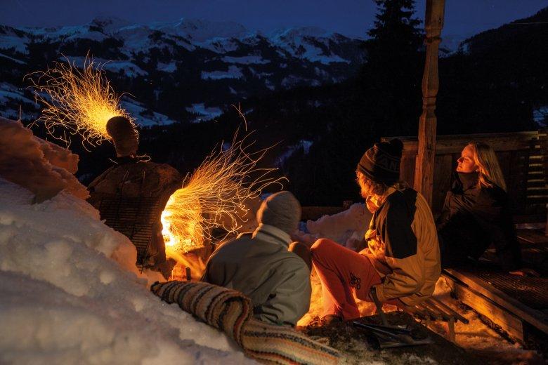 Feuer frei: Oskar, Baptiste und Lea heizen den Ofen vor der Hütte ein.