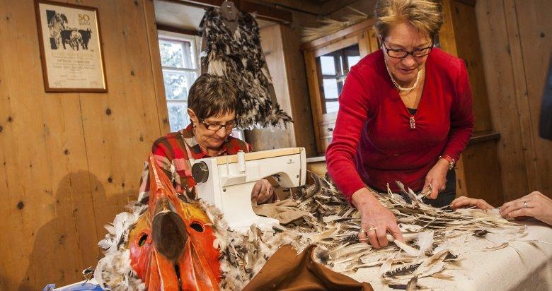 Der Giggeler:In akribischer Handarbeit schmücken die Frauen das Kostüm für den Giggeler mit Federn.