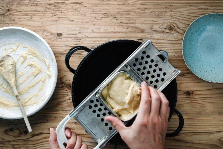 Schritt 2: Den Teig durch ein Spatzlsieb in kochendes Salzwasser drücken.
