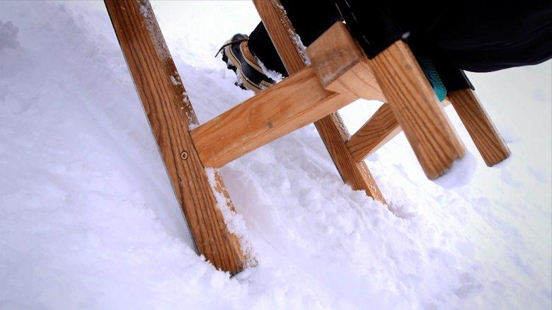 Zum Bremsen beide Füße neben den Kufen in den Schnee drücken.